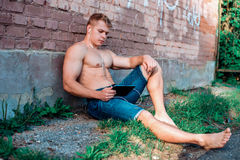 Ένας σύγχρονος αρσενικός αθλητής στα σορτς κάθεται στην οδό με μια ταμπλέτα και τα ακουστικά, προσέχοντας έναν κινηματογράφο στα  Στοκ Εικόνες