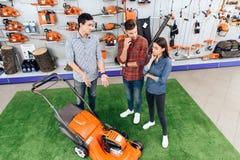 Ένας σύμβουλος σε ένα κατάστημα εργαλείων κήπων παρουσιάζει σε έναν τύπο και σε ένα κορίτσι θεριστή χορτοταπήτων Στοκ Εικόνες