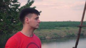 Ένας τακτοποιημένος τύπος με μια αλυσίδα στην κόκκινη μπλούζα φαίνεται ένα πράσινο, όμορφο δέντρο, άλλη πλευρά, ποταμός, φύση, χλ απόθεμα βίντεο
