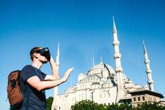 Ένας ταξιδιώτης με τα γυαλιά εικονικής πραγματικότητας Η έννοια του εικονικού ταξιδιού σε όλο τον κόσμο Στο υπόβαθρο το μπλε Στοκ φωτογραφία με δικαίωμα ελεύθερης χρήσης