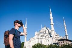 Ένας ταξιδιώτης με τα γυαλιά εικονικής πραγματικότητας Η έννοια του εικονικού ταξιδιού σε όλο τον κόσμο Στο υπόβαθρο το μπλε Στοκ Εικόνες
