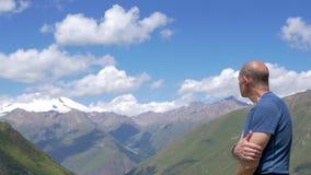 Ένας ταξιδιώτης στέκεται υψηλός στα βουνά και εξετάζει την κορυφή Elbrus απόθεμα βίντεο