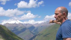 Ένας ταξιδιώτης στέκεται υψηλός στα βουνά και εξετάζει την κορυφή Elbrus φιλμ μικρού μήκους