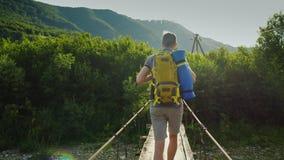 Ένας ταξιδιώτης με ένα σακίδιο πλάτης περπατά κατά μήκος μιας wobbly γέφυρας πέρα από έναν ποταμό βουνών υποστηρίξτε την όψη απόθεμα βίντεο