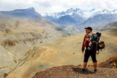 Ένας ταξιδιώτης με ένα σακίδιο πλάτης στα βουνά Himalayan εξετάζει το φαράγγι Νεπάλ Βασίλειο του ανώτερου μάστανγκ Στοκ Εικόνες