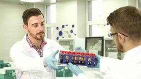 Ένας τεχνικός εργαστηρίων παραδίδει τους σωλήνες δοκιμής στο συνάδελφό του για τις έρευνες στοκ εικόνα