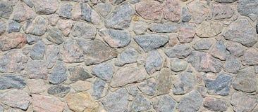 Ένας τοίχος πετρών, που τσιμεντάρεται γκρίζος μεταξύ των στρογγυλευμένων πετρών Backgrou Στοκ Φωτογραφία