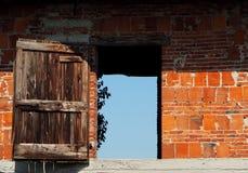 Ένας τουβλότοιχος με μια παλαιά ξύλινη πόρτα ανοικτή στον ουρανό Στοκ εικόνα με δικαίωμα ελεύθερης χρήσης