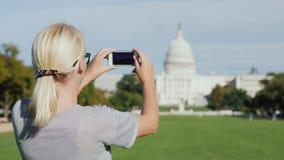 Ένας τουρίστας γυναικών παίρνει τις εικόνες του κτηρίου Capitol στην Ουάσιγκτον Τουρισμός στην ΑΜΕΡΙΚΑΝΙΚΗ έννοια φιλμ μικρού μήκους