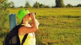 Ένας τουρίστας γυναικών στέκεται σε ένα δασικό ξέφωτο και κοιτάζει μέσω των διοπτρών πού να πάει έπειτα απόθεμα βίντεο