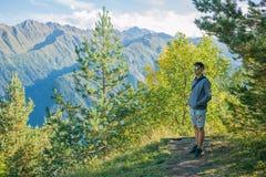 Ένας τουρίστας στα σορτς και μια μπλούζα που στέκεται πάνω από έναν απότομο βράχο στο υπόβαθρο των δέντρων και που προσέχει τον ό Στοκ Φωτογραφία