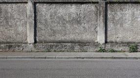 Ένας τραχύς συμπαγής τοίχος με ένα γκρίζο πεζοδρόμιο και έναν δρόμο ασφάλτου Αστικό υπόβαθρο για το διάστημα αντιγράφων στοκ εικόνες