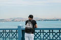 Ένας τύπος ή ένας νέος αρσενικός τουρίστας στέκεται στη γέφυρα Galata και απολαμβάνει την όμορφη θέα του Bosphorus και Στοκ εικόνα με δικαίωμα ελεύθερης χρήσης