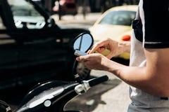 Ένας τύπος ή ένας τουρίστας ενεργοποιεί ή νοικιάζει ένα ηλεκτρικό μηχανικό δίκυκλο χρησιμοποιώντας μια κινητή εφαρμογή σε ένα τηλ στοκ φωτογραφίες με δικαίωμα ελεύθερης χρήσης