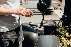 Ένας τύπος ή ένας τουρίστας ενεργοποιεί ή νοικιάζει ένα ηλεκτρικό μηχανικό δίκυκλο χρησιμοποιώντας μια κινητή εφαρμογή σε ένα τηλ στοκ εικόνα με δικαίωμα ελεύθερης χρήσης