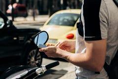 Ένας τύπος ή ένας τουρίστας ενεργοποιεί ή νοικιάζει ένα ηλεκτρικό μηχανικό δίκυκλο χρησιμοποιώντας μια κινητή εφαρμογή σε ένα τηλ στοκ φωτογραφία με δικαίωμα ελεύθερης χρήσης