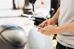 Ένας τύπος ή ένας τουρίστας ενεργοποιεί ή νοικιάζει ένα ηλεκτρικό μηχανικό δίκυκλο χρησιμοποιώντας μια κινητή εφαρμογή σε ένα τηλ στοκ εικόνες