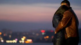 Ένας τύπος αγκαλιάζει στοργικά ένα κορίτσι ενάντια στο σκηνικό μιας πόλης νύχτας απόθεμα βίντεο