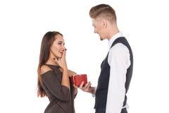 Ένας τύπος δίνει ένα δώρο στη φίλη του, το κορίτσι που στενοχωρείται χαίρεται για αυτό, χαμογελά απομονωμένος Στοκ Εικόνα