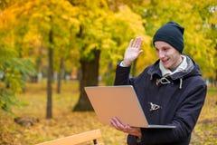 Ένας τύπος επικοινωνεί με κάποιο μέσω της τηλεοπτικής σύνδεσης μέσω ενός lap-top, το χαμόγελο και ο κυματισμός παραδίδουν το πάρκ Στοκ φωτογραφία με δικαίωμα ελεύθερης χρήσης