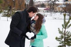 Ένας τύπος και ένα κορίτσι ζευγών αγάπης που κρατούν μια καρδιά του χιονιού Στοκ φωτογραφία με δικαίωμα ελεύθερης χρήσης