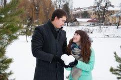 Ένας τύπος και ένα κορίτσι ζευγών αγάπης που κρατούν μια καρδιά του χιονιού Στοκ Φωτογραφίες