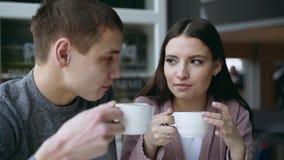 Ένας τύπος και ένα κορίτσι κάθονται μαζί σε έναν καφέ Πίνουν το τσάι Είναι ερωτευμένοι ο ένας με τον άλλον αγάπη ζευγών απόθεμα βίντεο