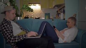 Ένας τύπος και ένα κορίτσι κάθονται στον καναπέ, οι εργασίες τύπων στον υπολογιστή, και χρησιμοποιεί το τηλέφωνο 4K φιλμ μικρού μήκους