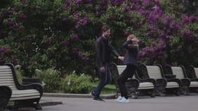 Ένας τύπος και ένα κορίτσι περπατούν στα χέρια εκμετάλλευσης ζώνης πάρκων Εραστές απόθεμα βίντεο
