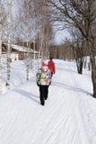 Ένας τύπος και ένα κορίτσι περπατούν στο πάρκο μια ηλιόλουστη χειμερινή ημέρα Στοκ Εικόνες