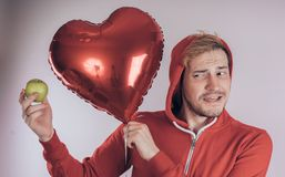 Ένας τύπος με ένα εύθυμο πρόσωπο κρατά την πράσινη Apple και ένα κόκκινο καρδιά-διαμορφωμένο μπαλόνι, σε ένα άσπρο υπόβαθρο Η ένν στοκ εικόνα