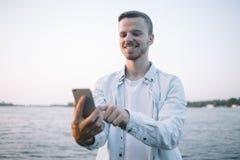 Ένας τύπος με ένα τηλέφωνο στο πάρκο Στοκ Φωτογραφία