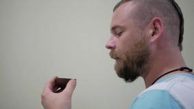 Ένας τύπος με μια γενειάδα και ένα τσάι κατανάλωσης mohawk puer από ένα κύπελλο απόθεμα βίντεο