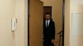 Ένας τύπος με μια γενειάδα σε ένα κοστούμι και έναν δεσμό στέκεται έξω από την πόρτα ενός διαμερίσματος και μιας ομιλίας 4K 4k βί φιλμ μικρού μήκους