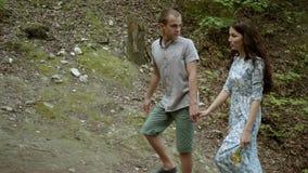 Ένας τύπος με τα χέρια μιας κοριτσιών εκμετάλλευσης που περπατούν μέσω του δάσους απόθεμα βίντεο