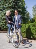 Ένας τύπος οδηγά το κορίτσι του σε ένα ποδήλατο Στοκ Εικόνες