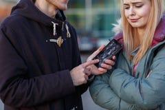 Ένας τύπος παρουσιάζει με δύο χέρια σπασμένο τηλέφωνο σε μια κινηματογράφηση σε πρώτο πλάνο κοριτσιών σε ένα θολωμένο υπόβαθρο Στοκ φωτογραφία με δικαίωμα ελεύθερης χρήσης