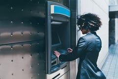 Ένας τύπος σε ένα επιχειρησιακό κοστούμι χρησιμοποιεί το ATM υπαίθρια στοκ φωτογραφίες