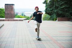 Ένας τύπος σε μια ΚΑΠ επιταχύνει την ώθηση του ποδιού του skateboard του Στοκ Φωτογραφίες