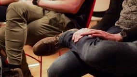 Ένας τύπος στο τζιν παντελόνι κάθεται στην καρέκλα και τρυπά το ρυθμό με τα δάχτυλα απόθεμα βίντεο