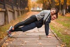 Ένας τύπος συμπιέζει από το έδαφος με ένα κορίτσι στην πλάτη του Υπαίθρια στο πάρκο φθινοπώρου στοκ εικόνα