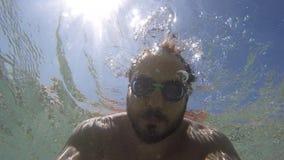 Ένας τύπος φαίνεται κάτι κάτω από τη θάλασσα απόθεμα βίντεο