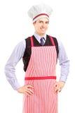 Ένας τύπος χαμόγελου με το μαγείρεμα της τοποθέτησης καπέλων και ποδιών Στοκ Εικόνες