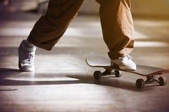 Ένας τύπος ωθεί από το πάτωμα και οδηγά skateboard στοκ εικόνα