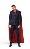 Ένας λυπημένος επιχειρηματίας σε ένα κόκκινο ακρωτήριο superhero που στέκεται με τους ώμους του κατρακύλησε και που κοιτάζει κάτω στοκ εικόνες