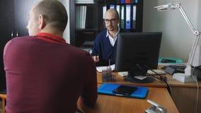 Ένας υφιστάμενος στο γραφείο του προϊσταμένου παρέχει την κανονική έκθεση σχετικά με την εργασία διενεργηθείσα φιλμ μικρού μήκους