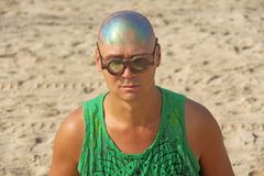 Ένας φαλακρός και ασυνήθιστος νεαρός άνδρας, ένας φρικτός, με λαμπρά φαλακρά επικεφαλής και στρογγυλά ξύλινα γυαλιά στο υπόβαθρο  στοκ εικόνες
