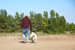 Ένας φαλακρός νεαρός άνδρας με ένα Λαμπραντόρ υπαίθρια στο δάσος Στοκ εικόνα με δικαίωμα ελεύθερης χρήσης