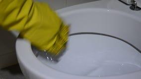 Ένας φορημένος γάντια καθαριστής πλένει την τουαλέτα απόθεμα βίντεο