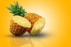 Ένας φρέσκος και πολύ juicy ανανάς μισός σε δύο μέρη στην πορτοκαλιά επιφάνεια στοκ εικόνες
